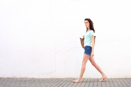 Full length portrait of smiling young woman with bag walking by white wall Stock Photo