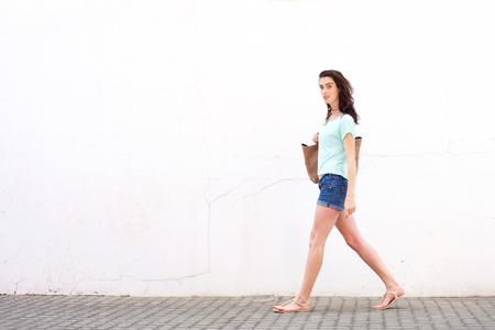 In voller Länge Porträt der lächelnden jungen Frau mit Tasche zu Fuß durch weiße Wand