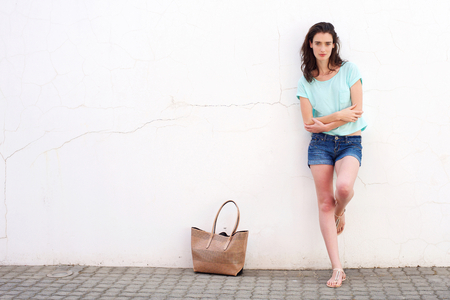 beautiful woman body: Full length portrait of fashionable young woman with purse leaning against white wall