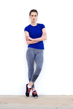 Full length portrait of serious sporty woman leaning against white wall with arms crossed