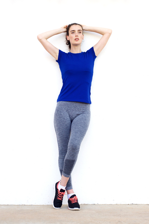 hands on head: Full length portrait of sporty woman leaning against white wall with hands behind head Stock Photo