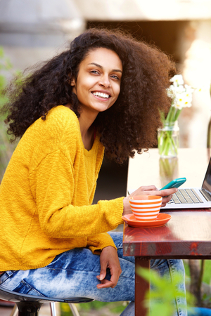 mujeres fashion: Portrait of cheerful african american lady sitting at outdoor cafe with mobile phone and laptop on table Foto de archivo