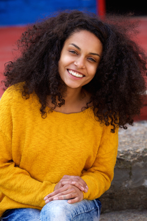 hair model: Close up portrait of beautiful young african lady with curly hair looking happy