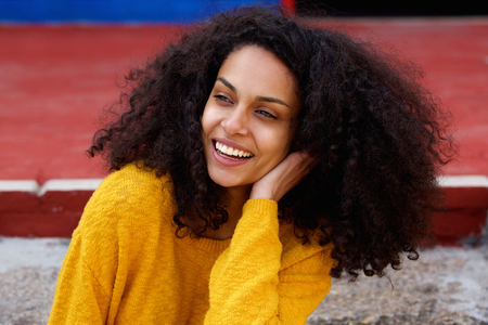 Close up portrait of young african lady with curly hair looking away and laughing