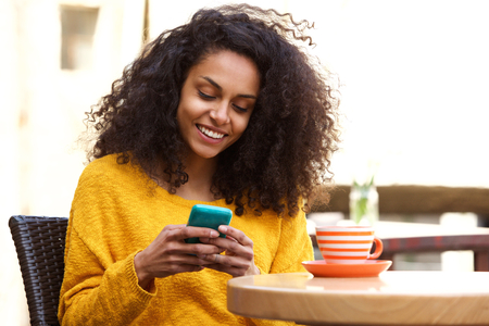 message: Close up portrait of beautiful young african american woman reading text message on mobile phone at coffee shop