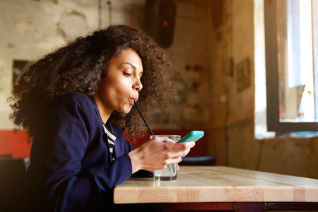 business woman phone: Close up side portrait of young african woman drinking juice in a coffee shop and reading text message on cellphone