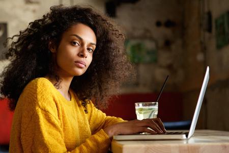 Nahaufnahmeporträt der ernsten jungen afrikanischen Frau, die an Laptop in einem Café arbeitet