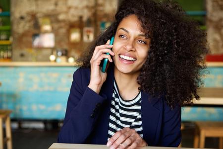 카페에서 핸드폰에 이야기하는 웃음 젊은 여자의 초상화를 닫습니다