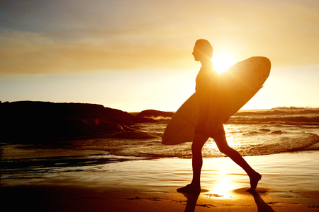 silueta masculina: Portrait of a surfer walking on beach with surfboard during sunset Foto de archivo