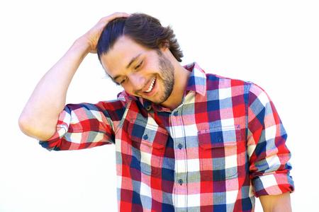 Retrato de hombre joven sonriente con la mano en el pelo