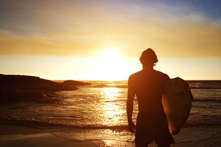 male surfer: Silhouette of male surfer watching the sunset at the beach