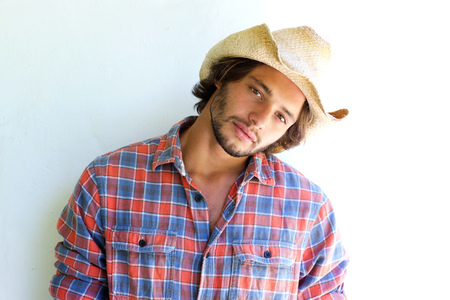 Close up portrait of rugged young man with plaid shirt and cowboy hat