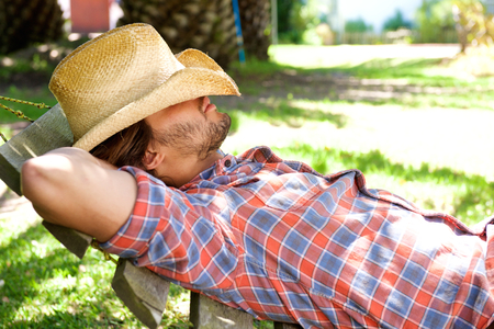 cowboy beard: Side portrait of young man lying on hammock resting with cowboy hat