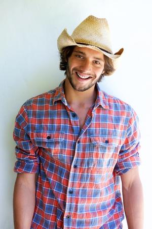 hombre con sombrero: Retrato de hombre joven y guapo sonriendo con sombrero de vaquero