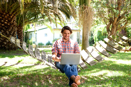 cool guy: Full body portrait of smiling young man sitting in hammock with laptop Stock Photo