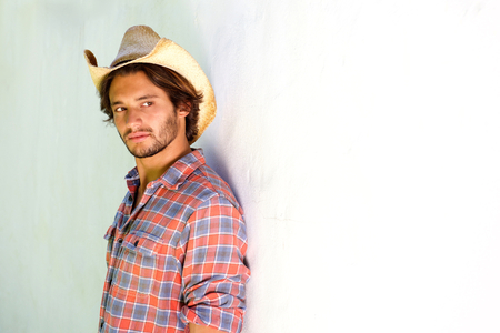 rugged: Portrait of rugged young man looking serious in cowboy hat