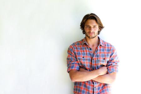 Ritratto di giovane uomo serio con le braccia incrociate su sfondo bianco