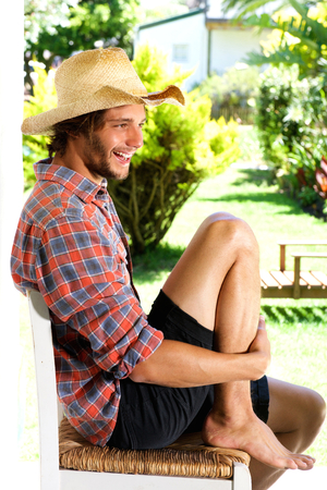 barefoot cowboy: Full body portrait of smiling young man wearing cowboy hat outside