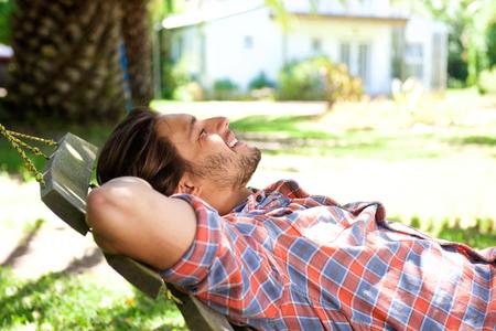Retrato de un hombre atractivo tumbado en la hamaca en el patio trasero