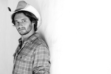 rugged man: Black and white portrait of rugged young man looking serious in cowboy hat