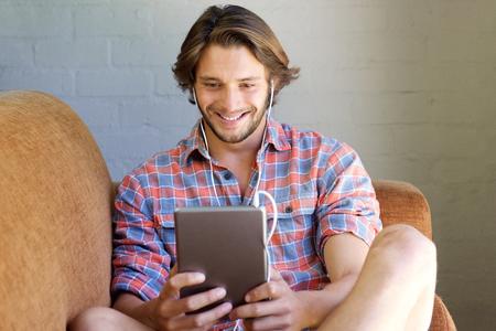 auriculares: Retrato de hombre joven sonriente viendo el video en la tableta con auriculares