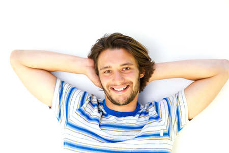 hands on head: Close up portrait of happy young man with hands behind head Stock Photo