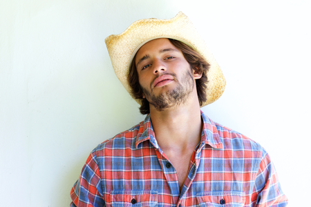 rugged: Close up portrait of rugged young man wearing cowboy hat