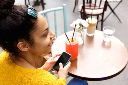 Sluit omhoog portret van jonge vrouwenzitting bij coffeeshoplijst