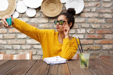 Portret van stijlvolle jonge Afrikaanse vrouw draagt een zonnebril zit op cafe en het nemen van selfie met haar smartphone Stockfoto