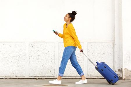 Zij portret van de vrouw reiziger met bagage en mobiele telefoon op straat in de stad