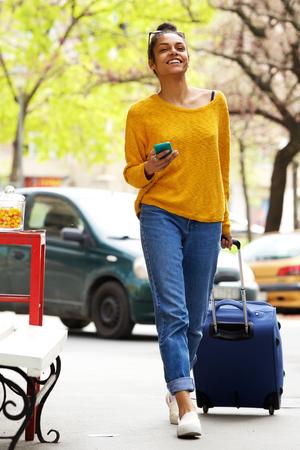 mujeres africanas: Retrato de cuerpo entero de la atractiva joven africana caminando con la maleta y el teléfono móvil en la calle de la ciudad