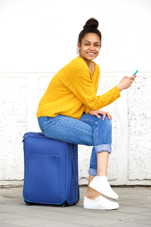 black lady: Portrait of cheerful young african woman sitting on travel bag with mobile phone
