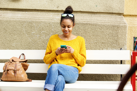 messages: Portrait of beautiful african woman sitting on bench and reading text message on her cell phone Stock Photo