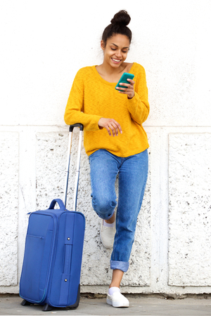 message: Portrait of cheerful african woman reading text message mobile phone and standing outside with suitcase Stock Photo