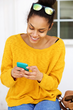 smile face: Portrait of smiling young woman sitting outside using mobile phone