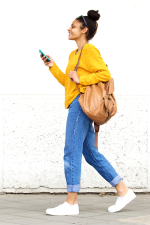 Full length side portrait of stylish young woman walking with bag and mobile phone