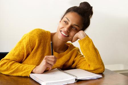 Portret van een glimlachende vrouwelijke student denken met met pen en papier
