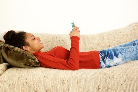 mujeres africanas: Perfil lateral de una mujer hermosa acostado en el sofá con el teléfono elegante