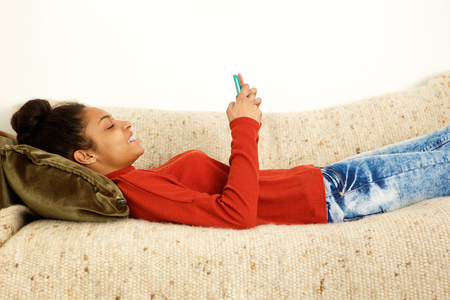 african women: Side profile of beautiful woman lying on couch with smart phone Stock Photo