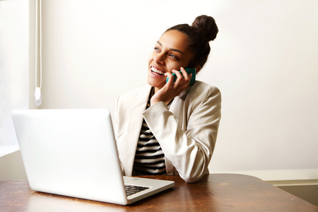 hp: Close up portrait of woman working with laptop and talking on cellphone Stock Photo