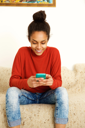 woman on phone: Portrait of an african american young woman using smart phone at home Stock Photo