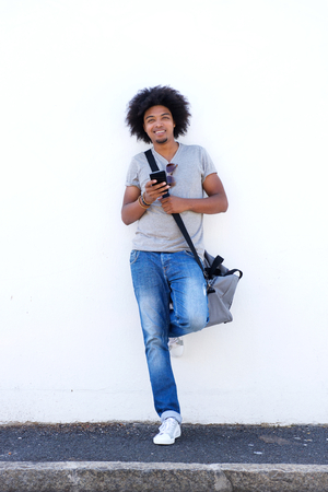 young guy: Full length portrait of a cool guy standing outside with cell phone and bag