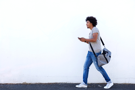male body: Full length portrait of a young man walking with bag and cell phone