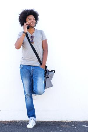 cuerpo hombre: Retrato de cuerpo entero de un hombre afroamericano sonriente hablando por teléfono móvil