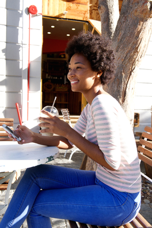 personas mirando: Side portrait of a young african woman sitting outside cafe with cell phone