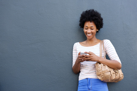 Portrait of smiling african woman with bag looking at mobile phone