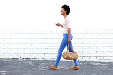 In voller Länge Portrait der schönen Frau zu Fuß im Freien Musik hören mit Geldbörse Standard-Bild - 59639470