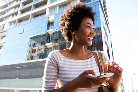 woman on phone: Portrait of a cheerful young woman standing in the city with cellphone Stock Photo