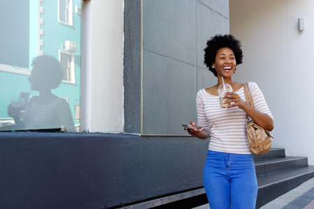 black lady: Portrait of happy woman walking with coffee and phone outside