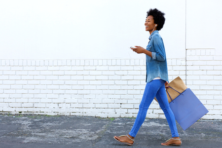 shopper: Side portrait of a smiling young woman walking with shopping bags and listening to music on smart phone Stock Photo